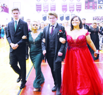 Zachary Murphy, Savannah Carrier, Jonathan Didier and Victoria Smith join together for a march down the Owen County High School gymnasium floor during Saturday's annual pre-prom Grand March. Saturday's prom was held at The Prickel Barn in Verona.
