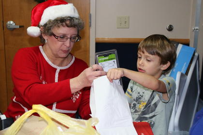 Machele Bess helps Brenton Goodrich package one of his gifts.