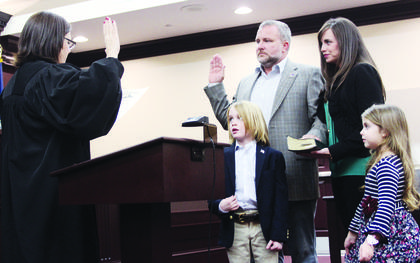 Owen County Judge-Executive Casey Ellis, accompanied by his wife Misty Bourne Ellis and children Fiona and Crosby Ellis, takes the oath of office following his win for a second term as the county's top elected official. The oath of office was administered by Circuit Judge R. Leslie Knight during a swearing-in ceremony Wednesday, Dec. 19.