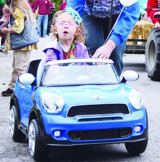 Lola Rotter takes her Mini Cooper for a spin during the parade Saturday.