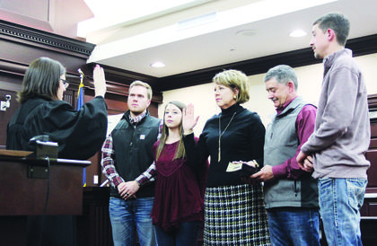 Owen County Circuit Clerk Margaret Forsee, third from left, takes the oath office accompanied by her son-in-law, Adam Weintraut, far left; daughter Morgan Weintraut; husband Brian Forsee, fourth from left and son Preston Forsee.