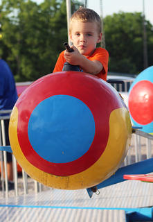 Micah Moore, 5, poses for the camera in one of the fair's many rides.