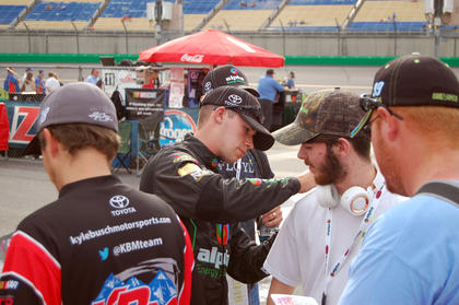 Louisville native Ben Rhodes signs the back of a fan's T-shirt after qualifying in ninth place.