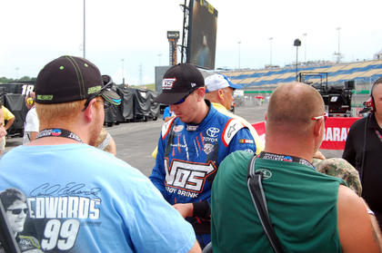 Kyle Busch takes a moment to sign autographs between qualifying for the truck race and the final practice session for the NASCAR Xfinity Series.