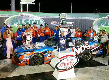 Kyle Busch hoists the Alsco 300 trophy above his head during victory lane celebrations on Friday night while wife Samantha, pictured at far left, takes pictures of the celebration.