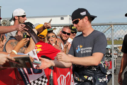 Dale Earnhardt Jr. signs autographs for fans at the track.