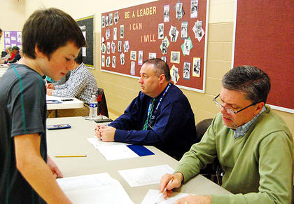 Superintendent Rob Stafford walks Lucas Lyons through the cost of student loan payments.