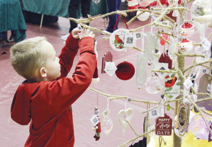 Cainnon Brumback looks at ornaments for sale during Saturday's Holiday Marketplace at Owen County High School, hosted by the Owen County Chamber of Commerce.