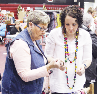 Jamie Moore, right, shows Lois Wainscott a few pieces of jewelry for sale at her booth.