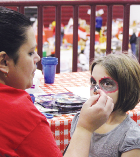 Karma Paliobagis gets her face painted at the Kids Zone.