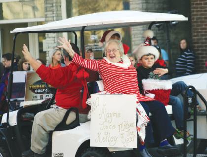 Mayme Kelley, the 2017 Owen County Mother of the Year, waves to parade goers from the back of a golf cart driven by Billy O'Banion.