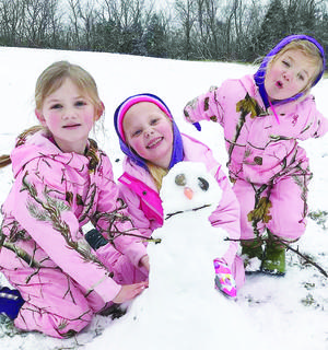 Decked out in matching snow gear, Harper Porter, Mallorie Tate and Rowan Porter pose with a snowman