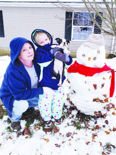 Barbara Brumley, granddaughter Dani Brumley and dog Buster with Dani's first snowman.