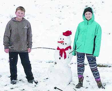 Maggie and TJ Ponder with their snowman created Jan. 12.