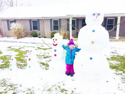 Aubrey Craigmyle enjoys the first snow of 2019 with a family of four snow people.