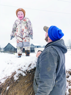 Jordan Shelton, right, watches his son, Jase Shelton, play on a bale of hay during the first snow of 2019 Jan. 12, in Wheatley. While the snow was quick to melt, a light dusting of snow Monday forced Owen County Schools to close for the day.