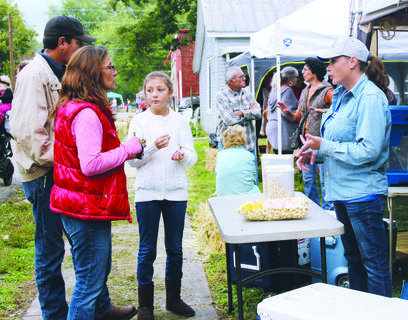 Wendy, George and Alleah Morales chat with Linda Carter, who was running a kettle corn stand Saturday.